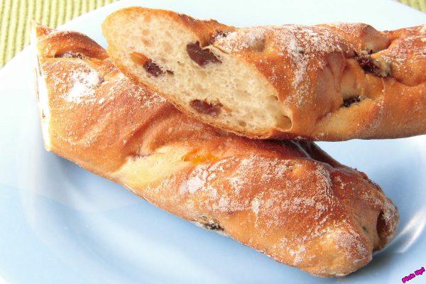 白い打ち粉をまぶされたスティック状のフランスパン。