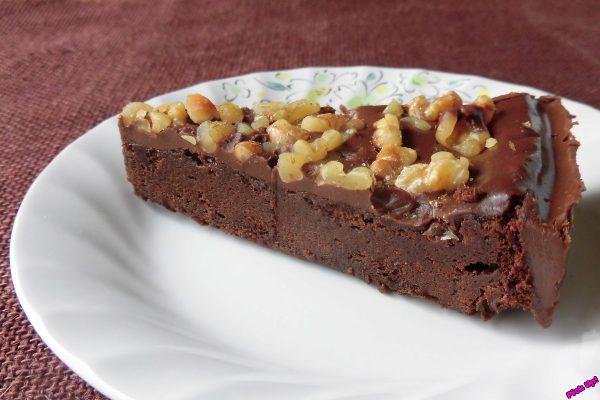 クルミがたっぷりトッピングされた、つやのあるチョコケーキの1ピース。