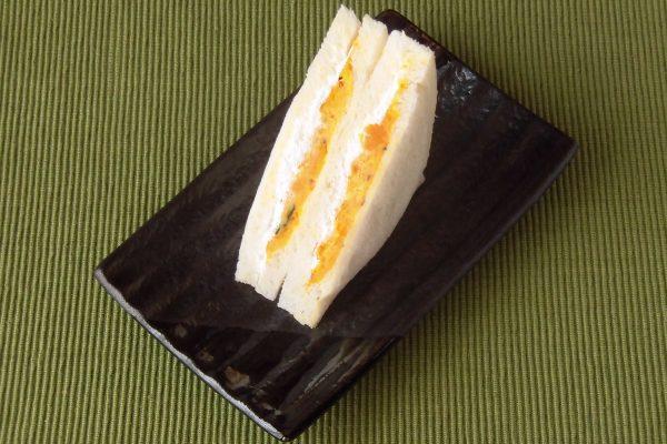 白いパンの間にひときわ白いホイップと、オレンジ色のパンプキンサラダ。